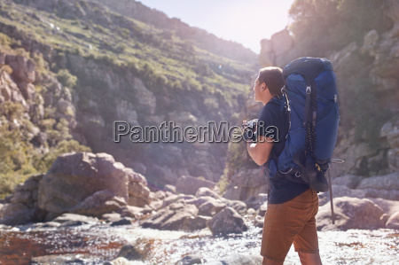 young man with backpack hiking photographing