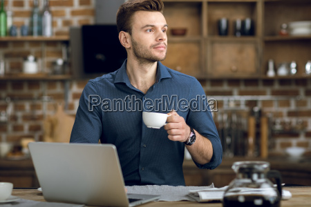 pensive young man with coffee cup