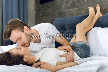 couple lying in bed man kissing