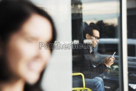 a seated man seen through a