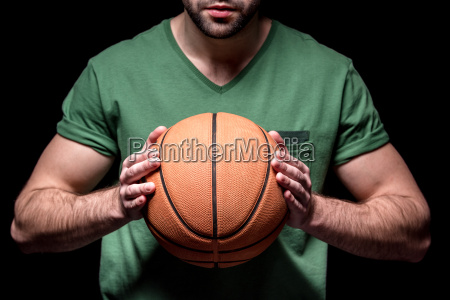 partial view of man holding basketball