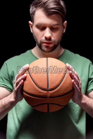 portrait of pensive man holding basketball