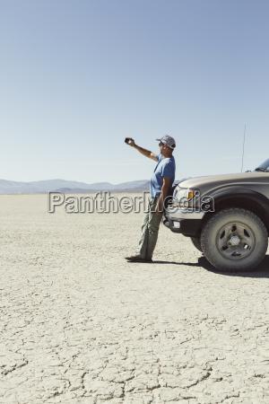 man leaving against truck in desert