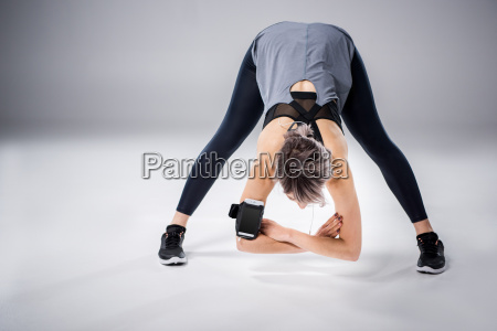 woman in sportive clothes stretching on