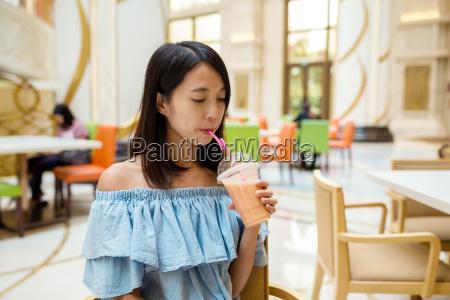 woman, enjoy, her, juice, in, restaurant - 20506643