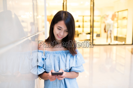woman, using, cellphone, in, shopping, mall - 20506649