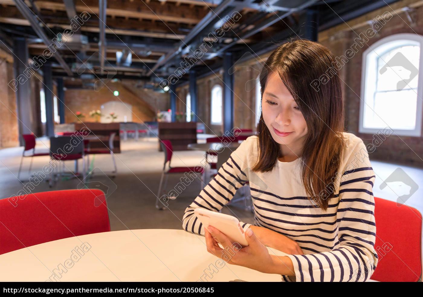 woman, using, cellphone, inside, restaurant - 20506845