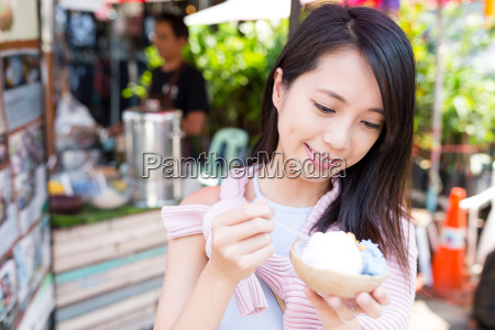 woman enjoy ice cream at street