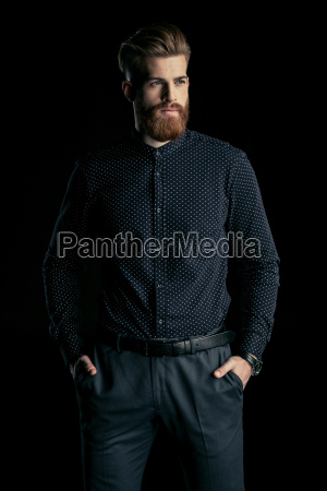 stylish handsome bearded man standing with
