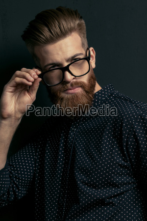 handsome bearded young man hipster adjusting