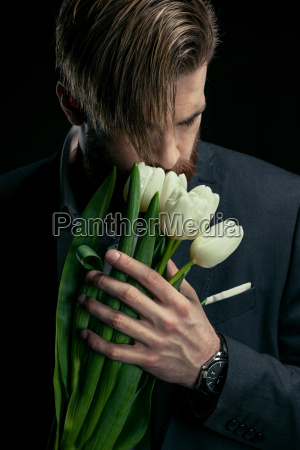 stylish businessman in suit holding tulips
