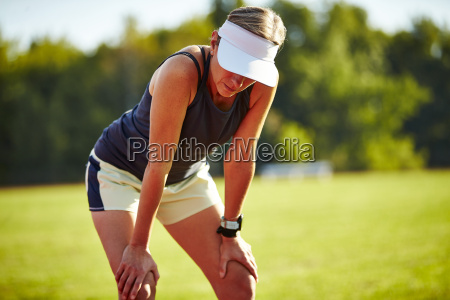a female runner catches her breathe