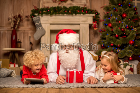 santa, claus, and, children, lying, on - 20509693