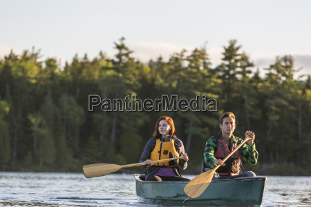 a young couple paddles a canoe