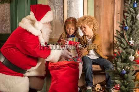 santa claus giving gift boxes to