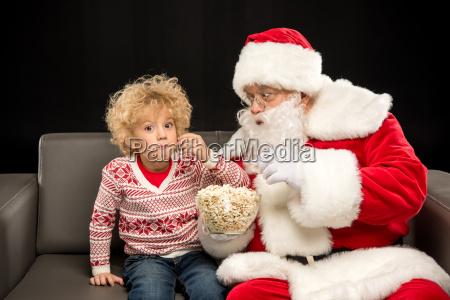 santa, claus, eating, popcorn, with, kid - 20512257