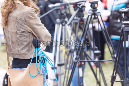 female reporter waiting for news conference