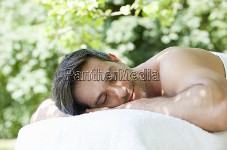 serene man laying on massage table