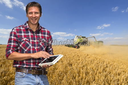farmer with digital tablet stands in