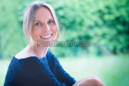 smiling blonde woman with window to