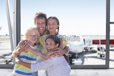 portrait of excited family in airport