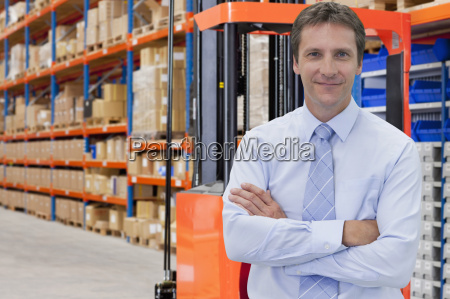 portrait of businessman in warehouse with