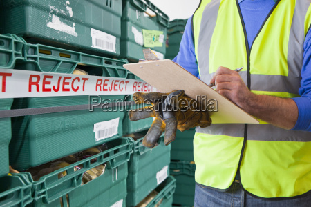worker with rejected produce in food