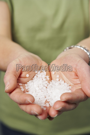 hands holding plastic polymer pellets