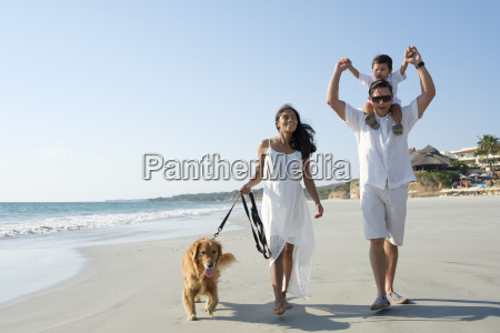family walking on the beach with