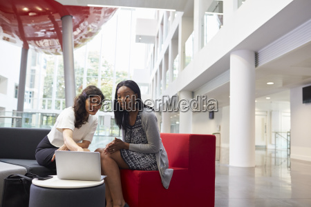 two businesswomen using laptop in lobby