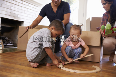 family unpacking boxes in new home