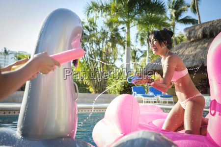 two women splashing with water guns