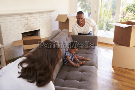 parents carry son on sofa into