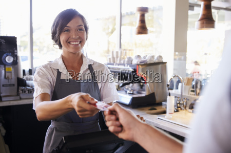 cashier accepts card payment from customer