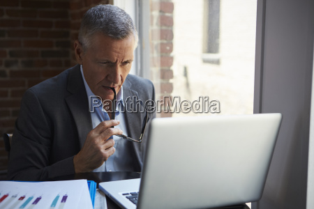 mature businessman working on laptop by