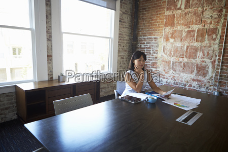 businesswoman studying document in boardroom