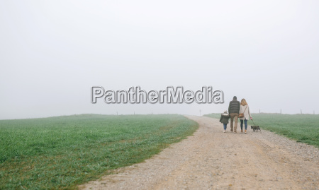 family walking with dog on a