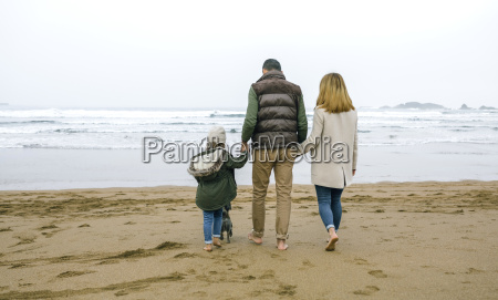 family walking with dog on the