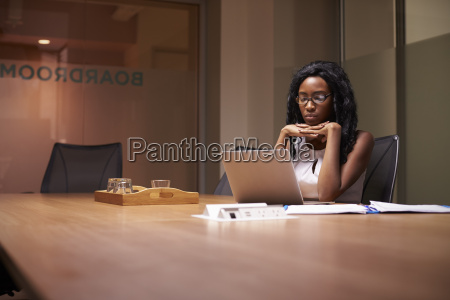 young black businesswoman working late alone