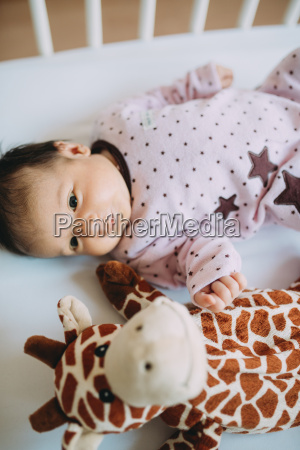 newborn baby girl lying in crib