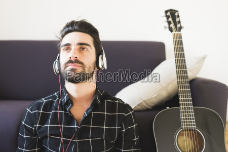 young man at home wearing headphones