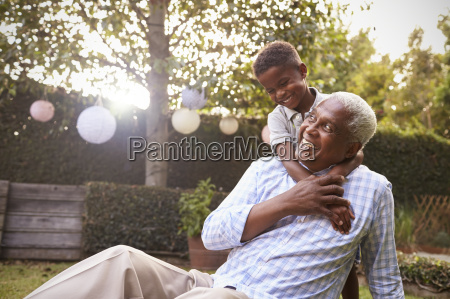 young black boy embracing grandfather sitting