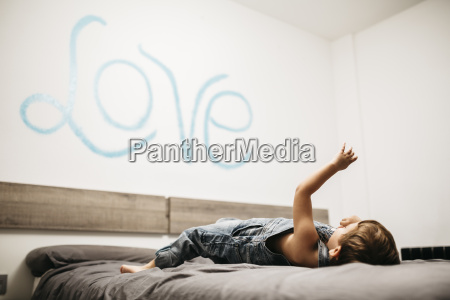 little boy playing on the bed