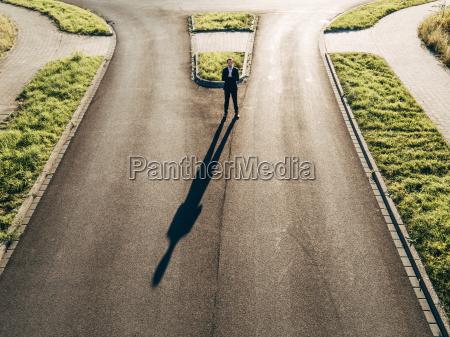 focused businessman standing on road