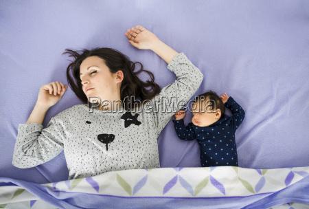 newborn baby girl and mother sleeping