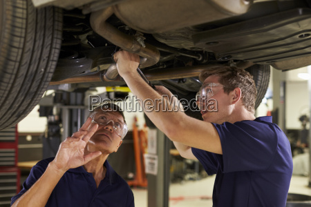 mechanic and male trainee working underneath