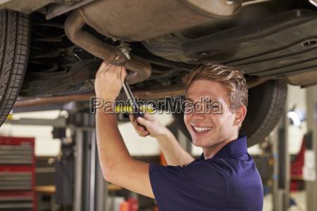 portrait of auto mechanic working underneath
