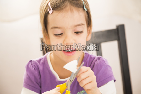 little girl tinlering at home cutting