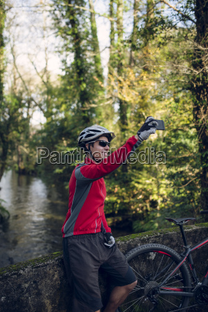 mountain biker taking picture in forest