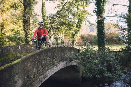 young mountain biker standing on bridge